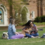 strumming a guitar on Alumni Lawn