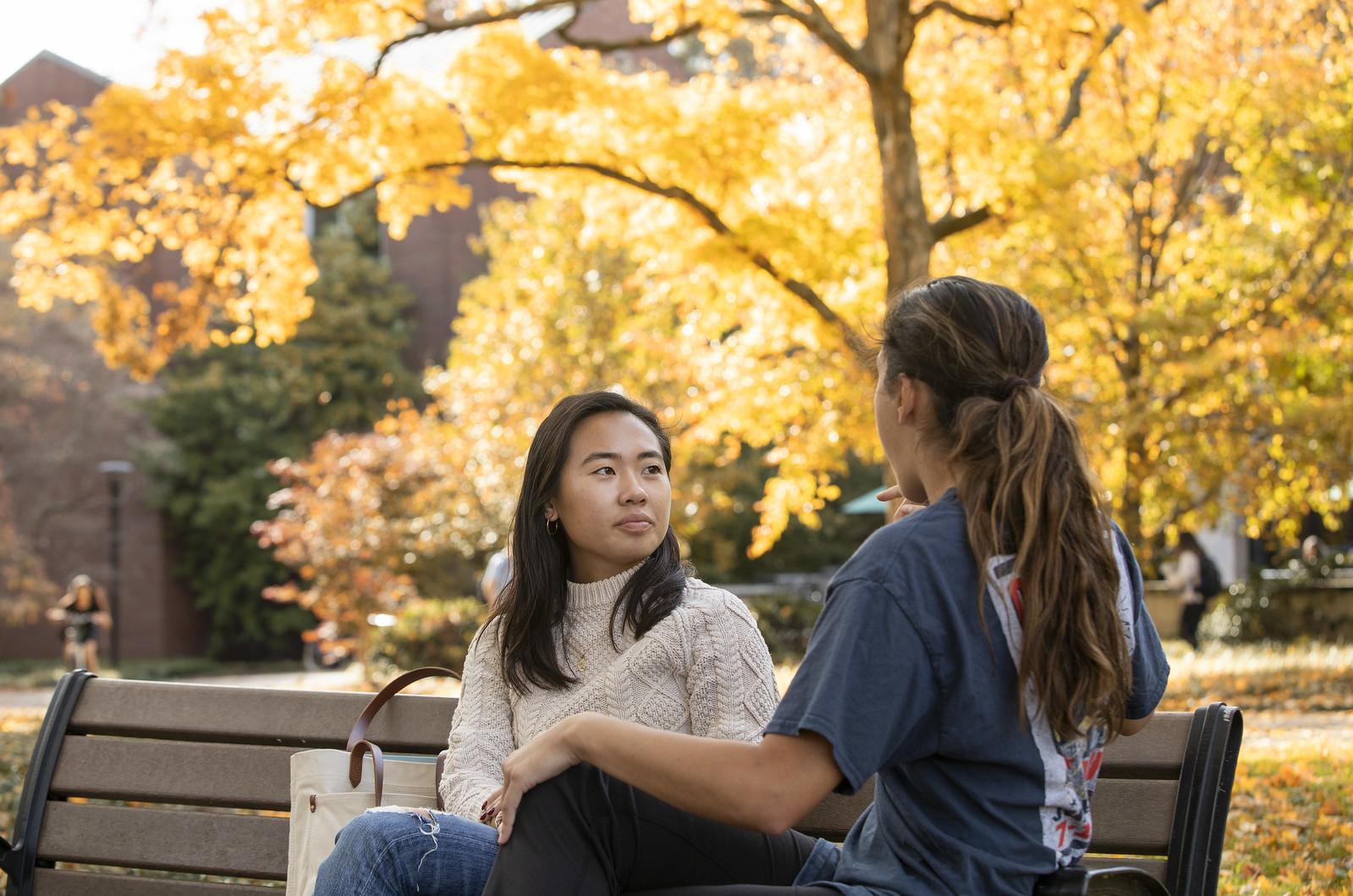 Vanderbilt students chatting on a campus bench