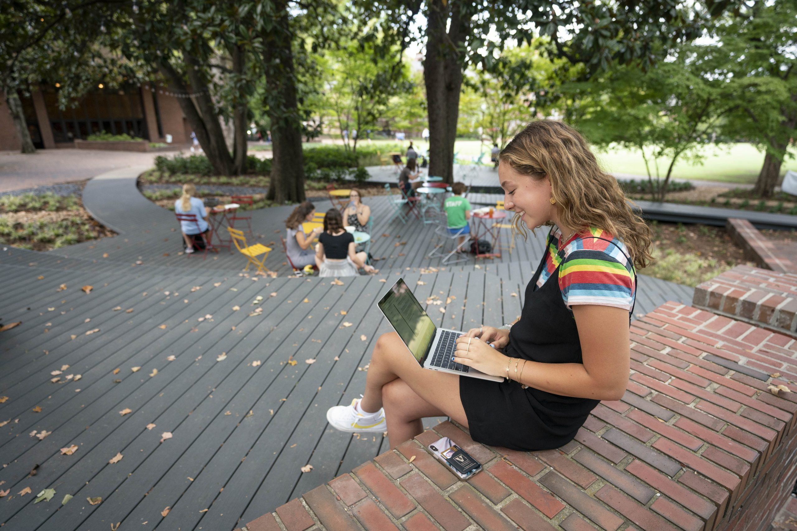 student working on a laptop outside on campus
