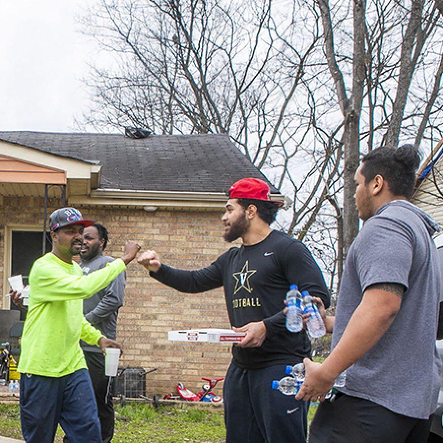 Vanderbilt senior, Mo Hasan, football teammates, and other students pass out meals and water for Nashville community in North Nashville after devastating tornado.  Vanderbilt University   Photo: Anne Rayner; VU
